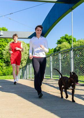 Coppia in esecuzione con il cane attraverso il ponte